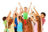 Šťastná dívka s zvednuté ruce ve skupině dětí