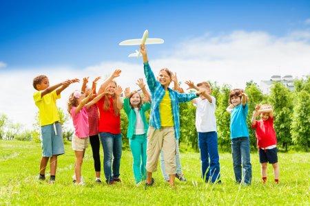 Photo pour Vue d'un enfant tenant un gros jouet d'avion blanc et d'enfants se tenant derrière sur le terrain pendant la journée d'été - image libre de droit