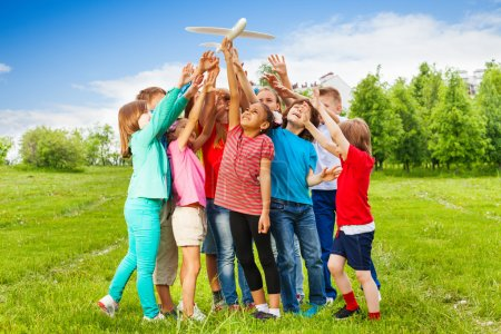 Group of kids reach after big white airplane toy