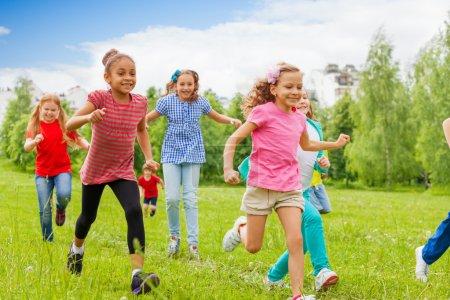 Group of happy kids running through green field
