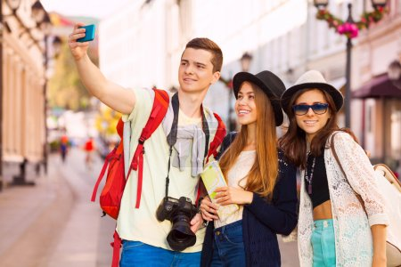 Photo for Girls and guy taking selfies with mobile phone during sightseeing on the European street during summer day time - Royalty Free Image