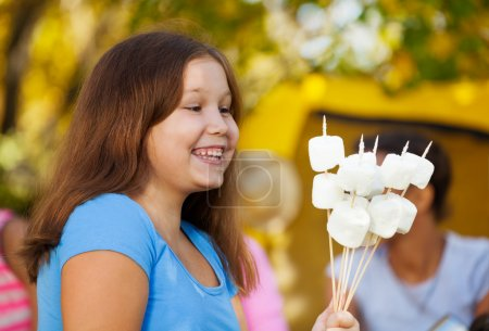 Girl holds sticks with marshmallow