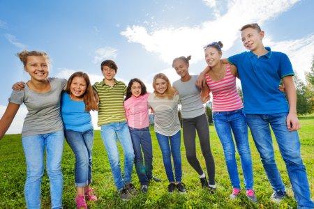 Photo pour Amis adolescents souriants debout sur l'herbe en rangée dans le parc pendant la journée ensoleillée d'automne sur fond de ciel - image libre de droit