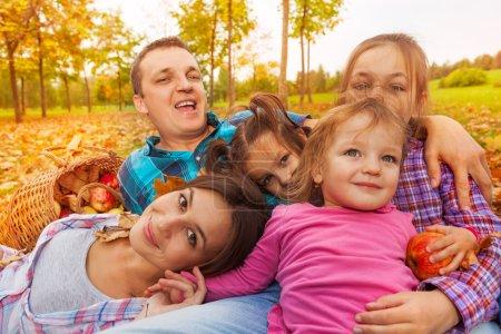 Photo pour Portrait en gros plan d'une grande famille avec un père mère et trois filles allongées dans les feuilles d'automne dans le parc - image libre de droit