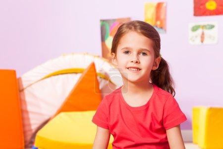 Photo pour Portrait de petite fille aux cheveux longs assis dans la chambre de la maternelle - image libre de droit