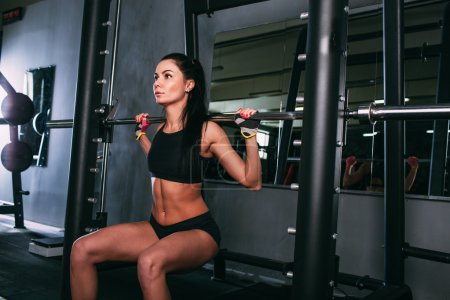 Photo for Brunette young sports woman doing squats with a barbell in Smith machine at the gym, front view - Royalty Free Image