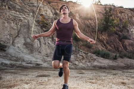 Photo for Sporty man jumping rope outdoors in the morning - Royalty Free Image