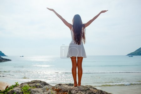 Photo pour Femme se tient sur des rochers en face de l'océan avec les mains en l'air - image libre de droit