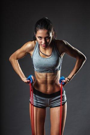 Photo pour Brunette athlétique femme exerçant avec du ruban en caoutchouc - image libre de droit