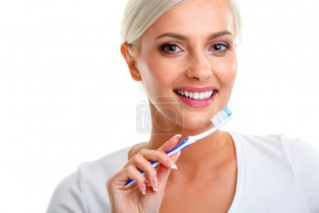 Photo for Closeup of beautiful young blonde lady holding toothbrush and smiling - Royalty Free Image