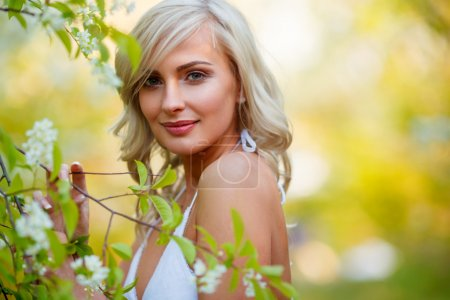 Photo for Beautiful blonde woman portrait in a flowered spring garden during sunset - Royalty Free Image