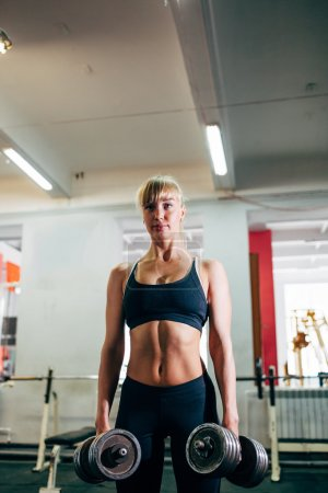 Strong fitness woman holding dumbbells