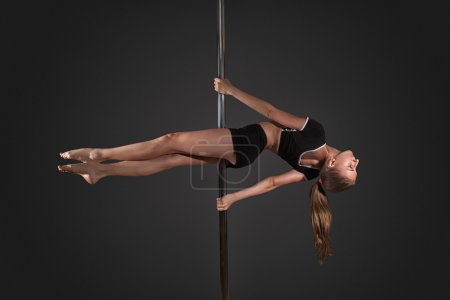 woman exercise pole dance on gray background