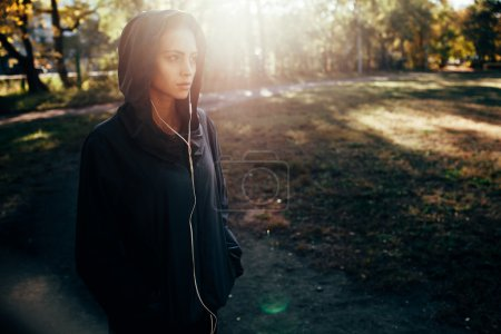 sporty woman wearing hood jacket and listening music