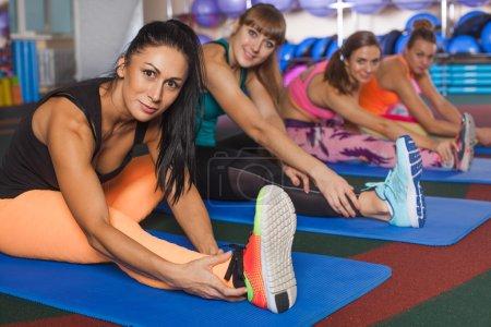 Photo pour Quatre femmes sportives qui s'étend de jambes sur les tapis dans la salle de gym - image libre de droit
