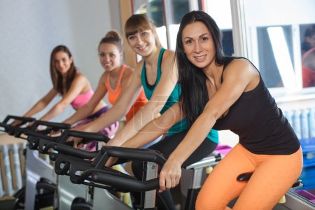 Group of four women in the gym cycling
