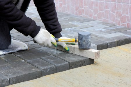 Worker installs paving slabs