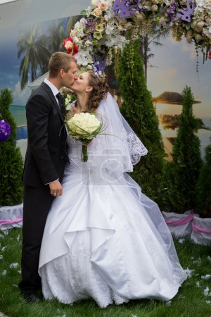 Photo for Young groom kiss bride and stand under floral wedding arch on marriage ceremony - Royalty Free Image
