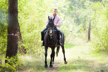 Photo for Handsome man in pink shirt ride on the black horse in green forest - Royalty Free Image