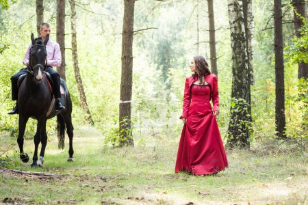 Photo for Young beautiful brunette girl in red dress walk and handsome man in pink shirt ride on the black horse in green forest - Royalty Free Image