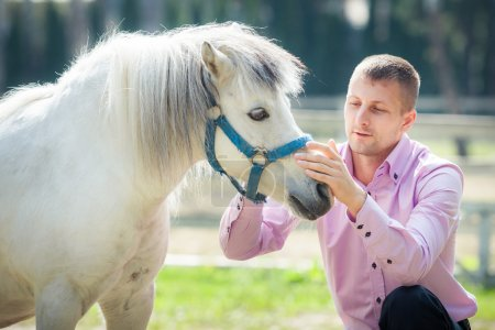 Photo for Handsome man in pink shirt sit near white pony horse on green field - Royalty Free Image