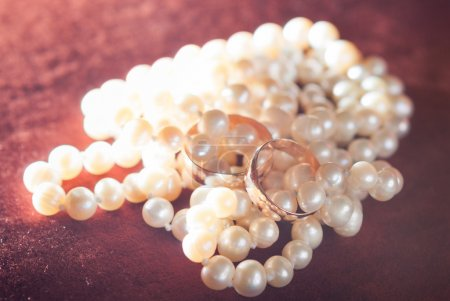 wedding rings on pearl necklace