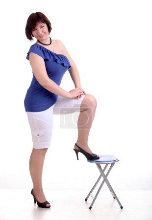 brunette fille en chemisier bleu et short blanc met un pied sur l