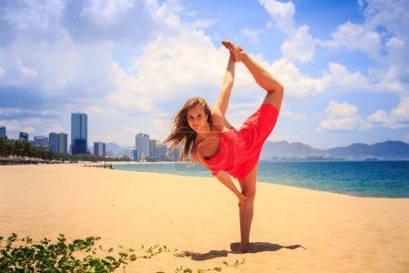 Photo pour Blond mince fille en robe rouge courte se tient en position gymnastique jambe échelle sur la plage de sable contre la mer azur et la ville - image libre de droit