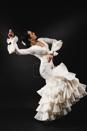 Photo for Young woman performing salsa dance with passion on black background - Royalty Free Image