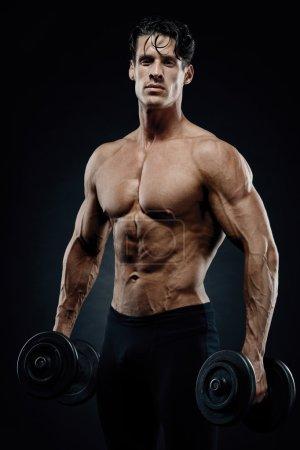 Handsome power athletic guy bodybuilder doing exercises