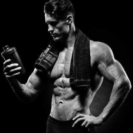 Muscular fitness male bodybuilder holding protein shake bottle