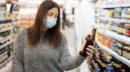 A woman in a protective mask stands in a supermarket near the shelves with groceries and looks at a glass bottle of beer in her hands. Shopping in a large store.