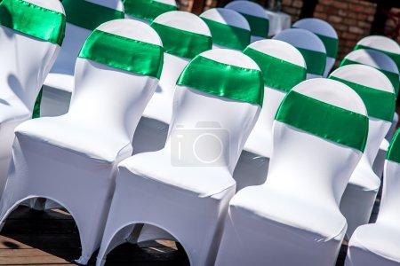 Photo pour Chaises de mariage blanches avec ruban vert à l'extérieur - image libre de droit
