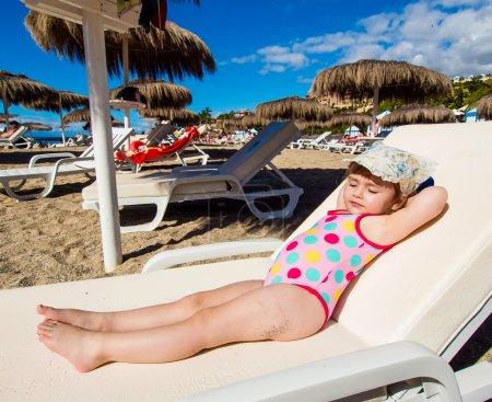 Adorable baby girl sunbathing on a deck chair on the beach