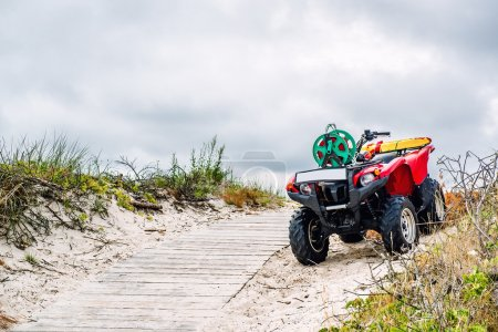 Quad bike parked on the sandy pathway to the Baltic Sea. Lithuania