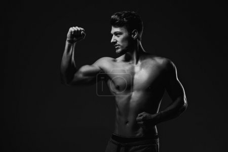 Photo for Athletic handsome man showing biceps muscles, studio shot. Black and white - Royalty Free Image