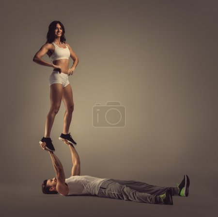Athletic couple doing acro yoga, studio shot