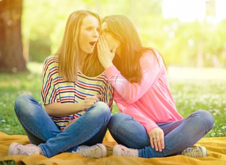 Photo for Two girl friends whispering secrets at park - Royalty Free Image