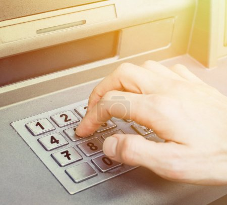 Hand entering PIN numbers on ATM bank machine