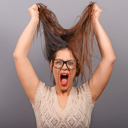 Portrait of a histerical woman pulling hair out against gray bac