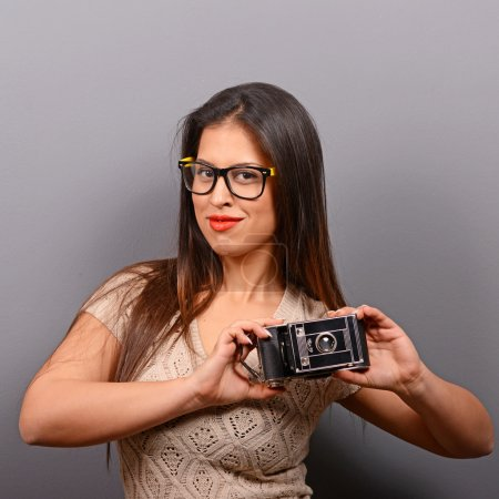 Portrait of a young woman holding retro camera against gray back