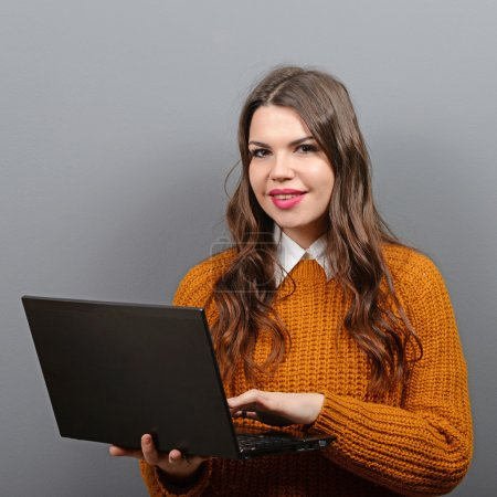 Portrait of woman using laptop against gray background