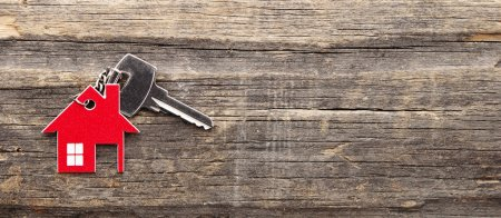 Photo for Symbol of the house with silver key on vintage wooden background - Royalty Free Image