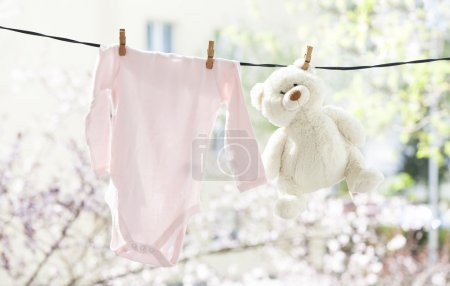 Photo for Baby clothes and teddy bear hanging on the clothesline - Royalty Free Image