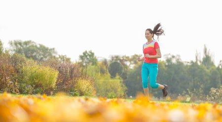 Female fitness model training outside.