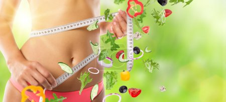 Photo for Slim girl measuring her waist with salad in motion. - Royalty Free Image