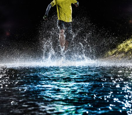 Single runner running, making splash in a stream.