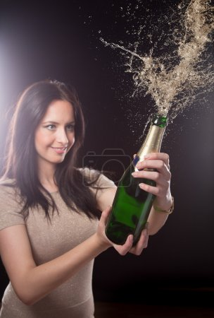 Photo for Young brunette woman with champagne bottle with explosion, celebration theme. - Royalty Free Image
