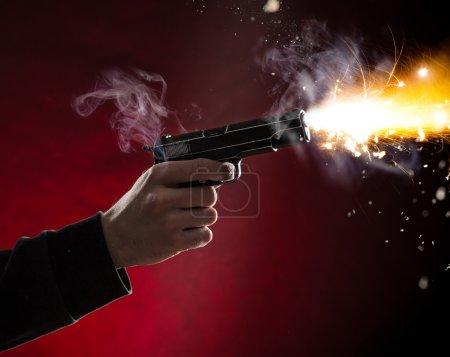 Killer with gun close-up on dark background...