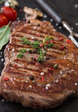 Photo pour Steak croustillant de boeuf sur table en pierre noire, gros plan . - image libre de droit